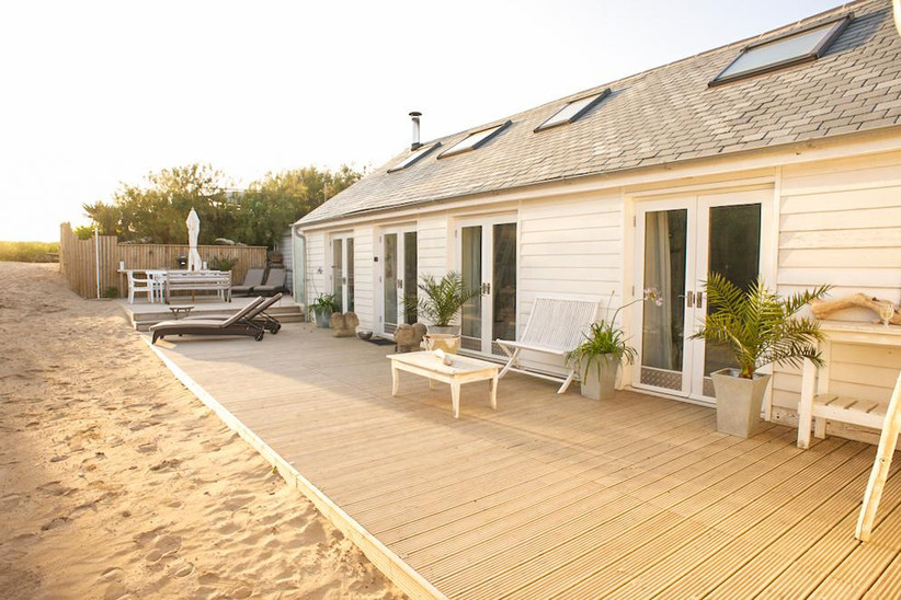 Cottage on the beach with decking and deckchairs