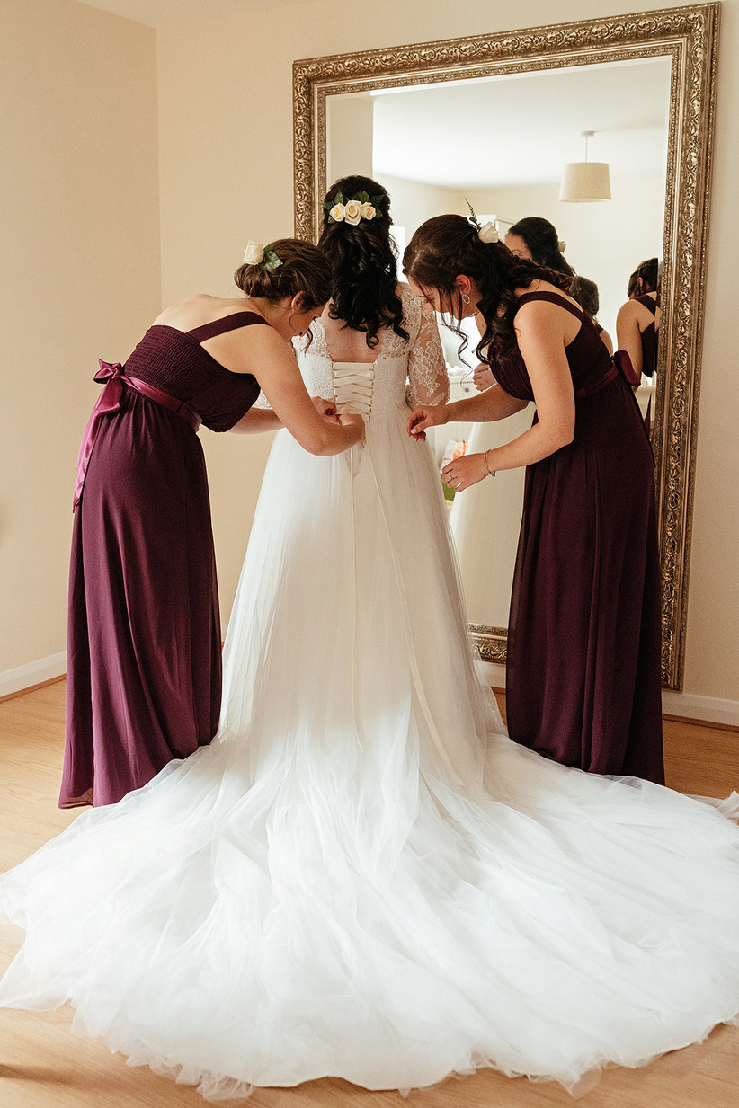 Becky's bridesmaids in burgundy dresses lacing up the back of her dress