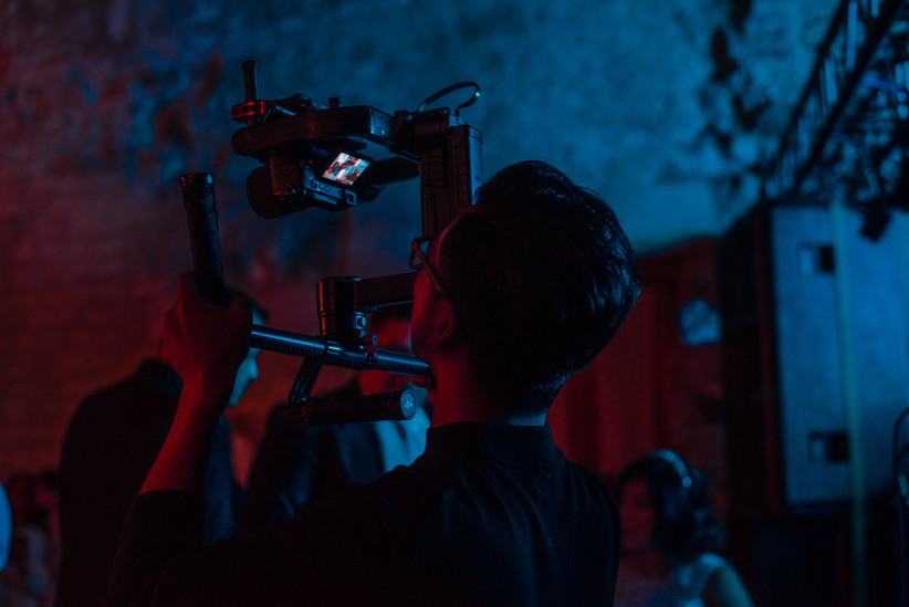 Male videographer filming the dance floor at a wedding reception