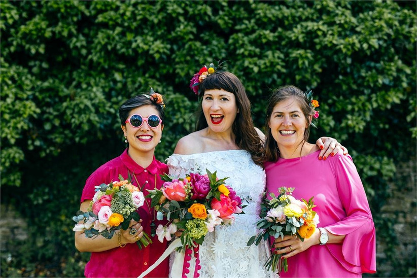 Bride standing with her bridesmaids wearing hot pink and holding bright flowers