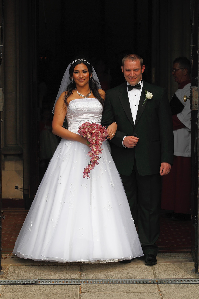 A half Filipino bride in a strapless white wedding dress and light pink bouquet links arms outside a church with her white husband who wears a tux