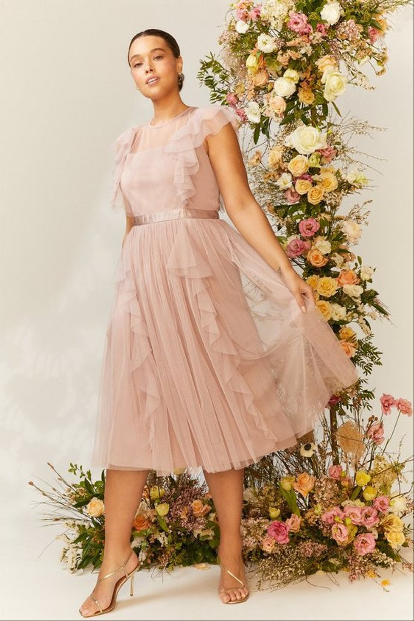 Girl wearing a nude ruffle mesh midi dress standing next to a tower of flowers