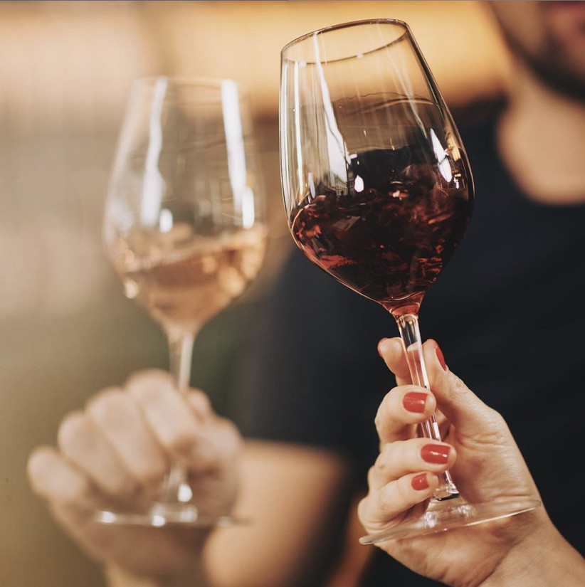 A woman and a man clinking full wine glasses