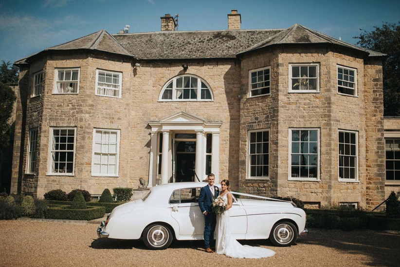 Bride and groom stand outside a country house with a vintage car