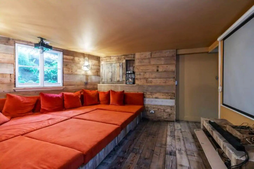 Cinema room with wooden walls and large orange seating