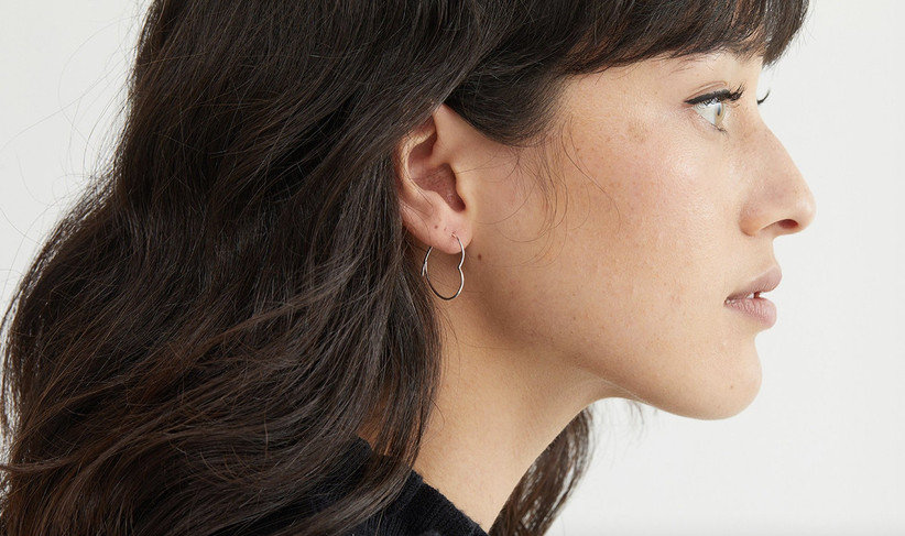 Side profile of a white woman with brunette hair and a fringe wearing heart shaped silver hoops and a flick of eyeliner
