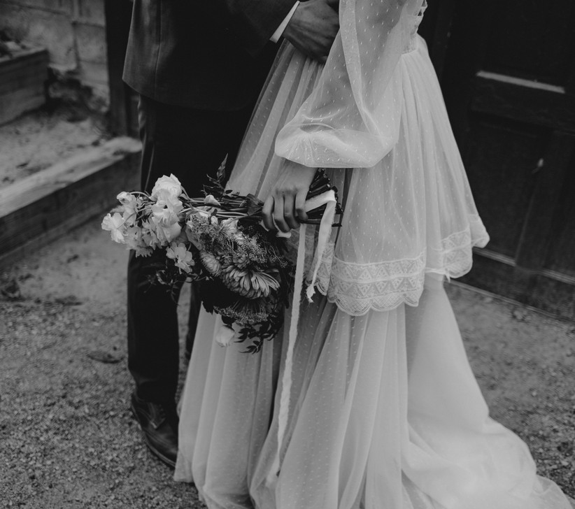 Black and white photo of the bottom half of a groom hugging a bride who is wearing a sheer, dotted multi-layered vintage style wedding dress and holding a wild bouquet