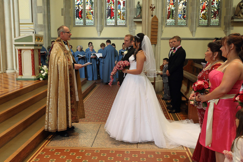 Bride in white with a pink bouquet and groom in a tux stand in front of a priest wearing gold at the top the aisle with family and a choir looking on