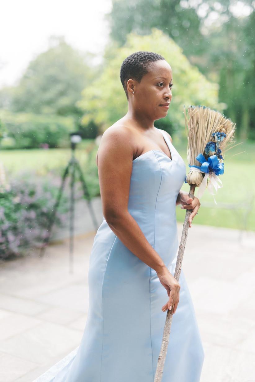 Bridesmaid holding a broom