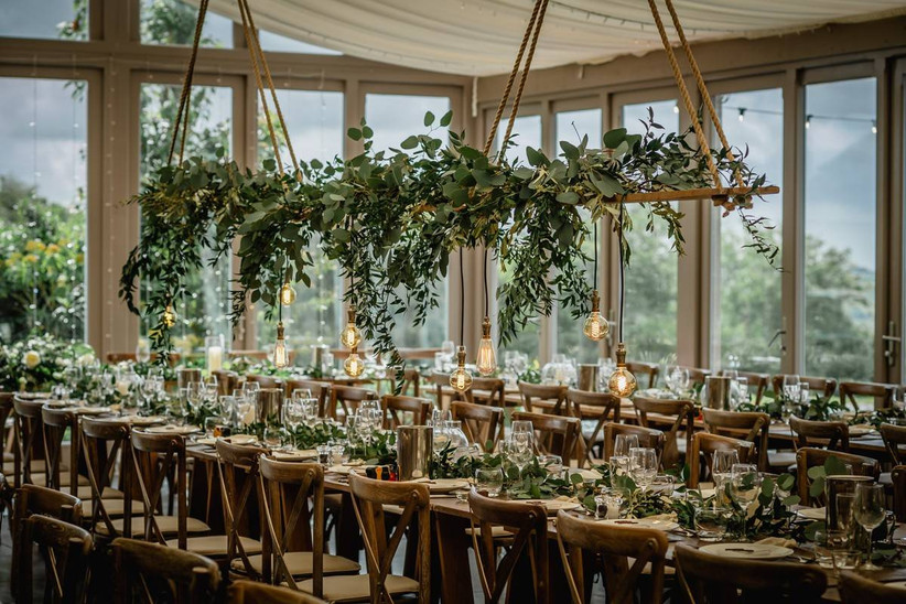 Dining area with wooden chairs and hanging greenery decorations and lightbulbs