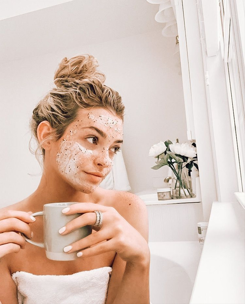 Girl in a towel with a bun holding a mug with a face mask on
