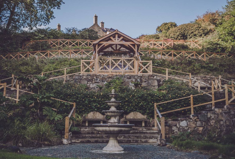 Stairs in a garden leading up to a wooden gazebo with a water fountain