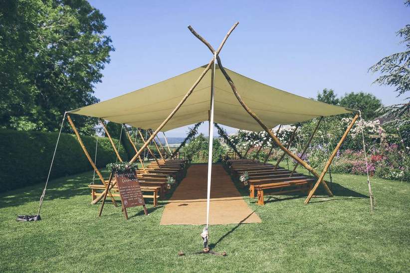 Marquee with wooden benches in a garden