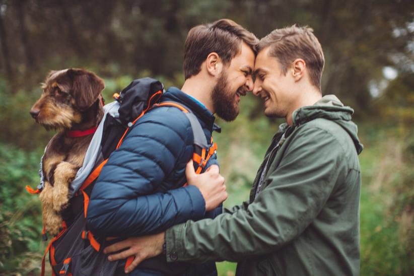 Gay couple walking their dog, celebrating marriage and anniversary