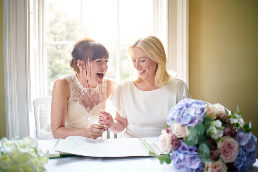 Two brides signing the wedding register