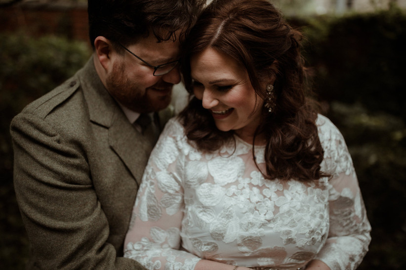 White bride with brunette half up hair, statement diamond earrings and a long sleeves high necked embroidered floral white wedding dress smiling next to her white bearded husband who wears a light green tweed suit