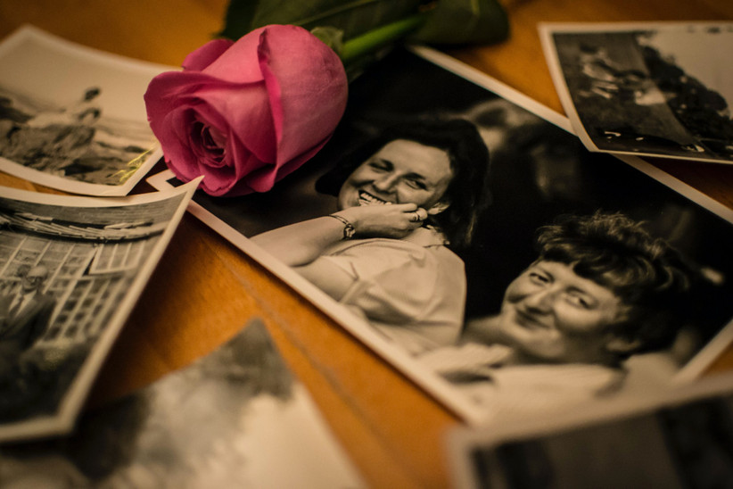 Black and white family photos spread out on a wooden memory table with a bright pink rose over the top