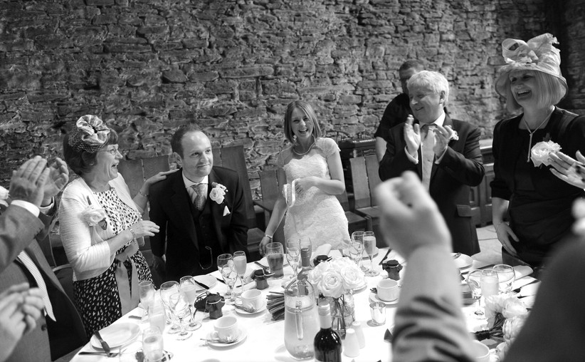 Black and white shot of the bride and groom laughing and taking a seat at the top table while family and friends clap