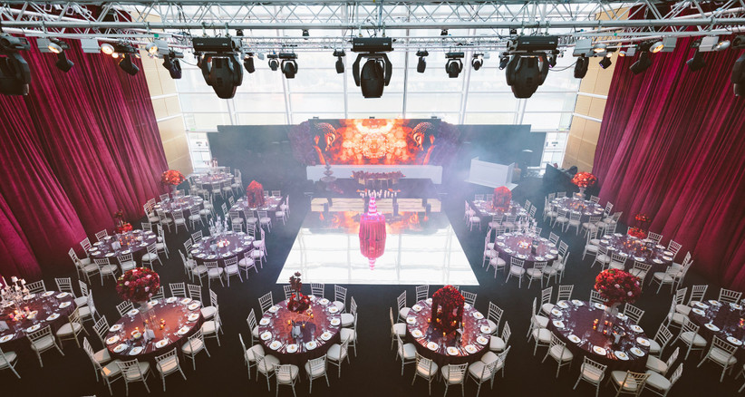 Reception room set up with lots of round tables and a stage