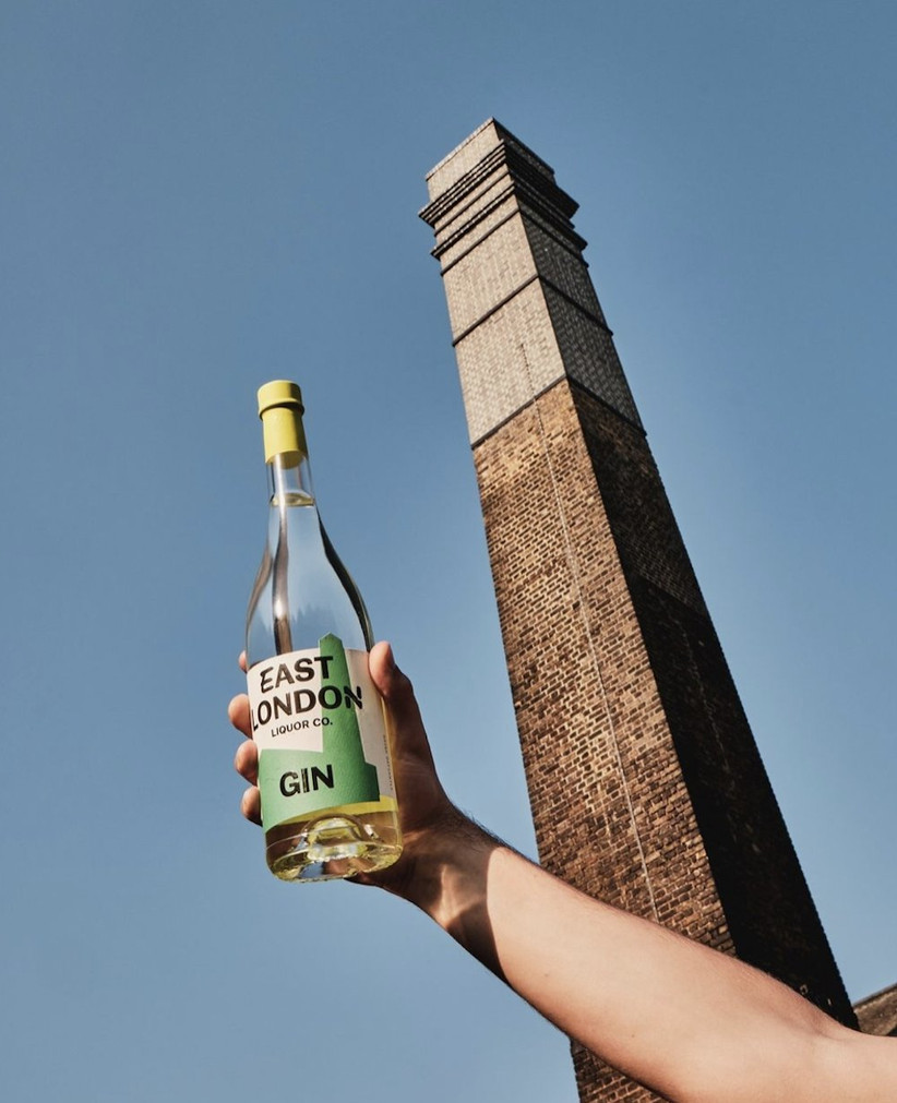 A man's hand holding a bottle of East London Liquor Co Gin against a blue sky and brick tower