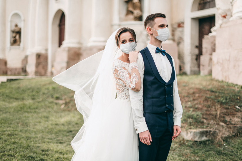 Bride and groom wearing protective face masks