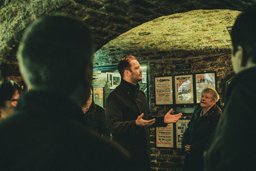 Bearded white man in a black coat giving a tour of The Cavern Club