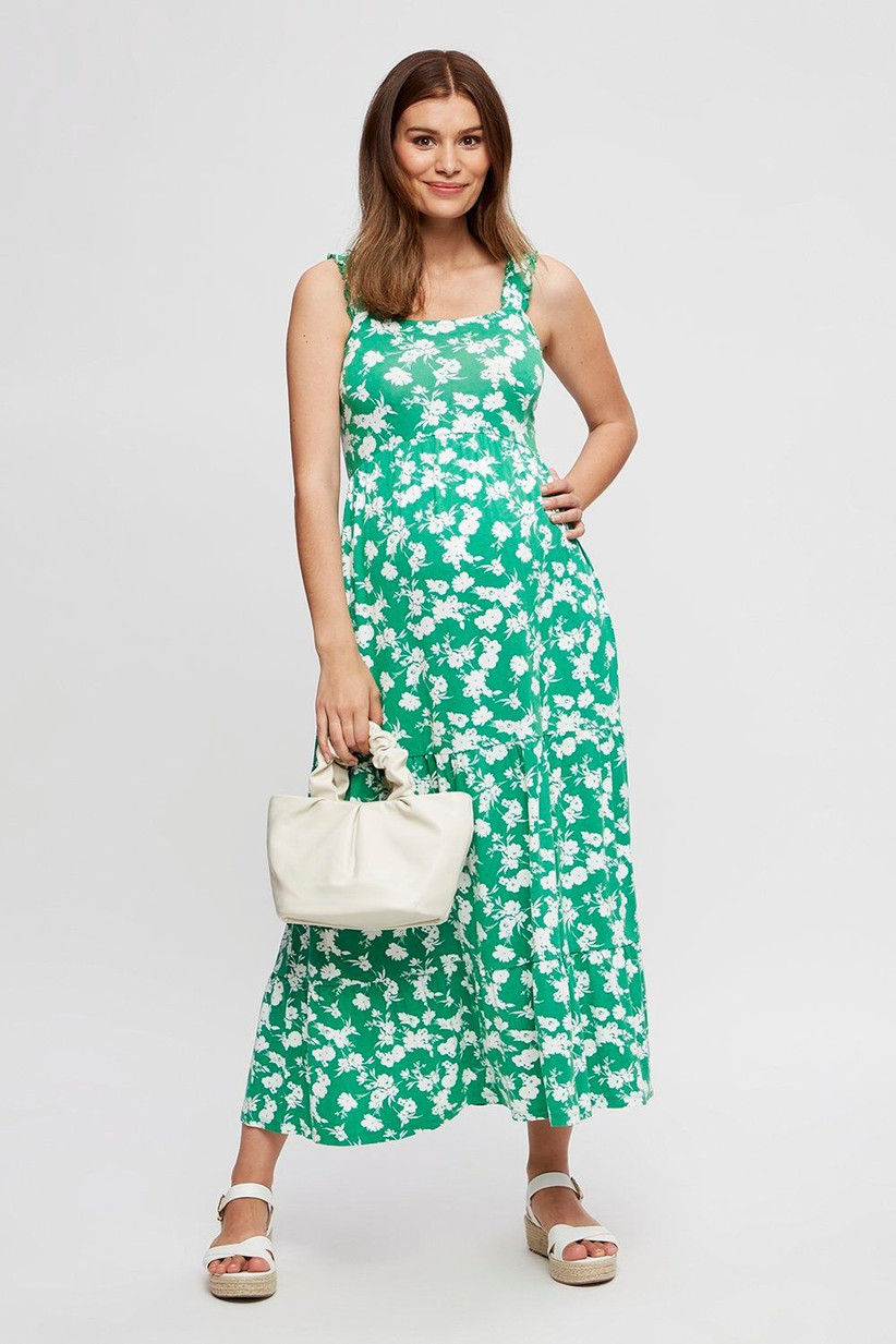 Pregnant model wearing a green floral wedding guest dress
