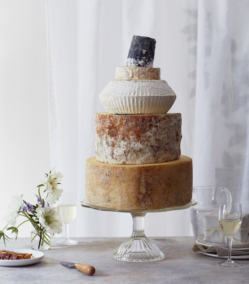 Stack of three different sized wheels of cheese on a cake stand with a vase of flowers to the left and glass of white wine on the right