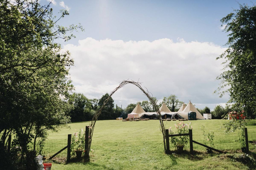 Wedding tipis in a field with a wooden arch