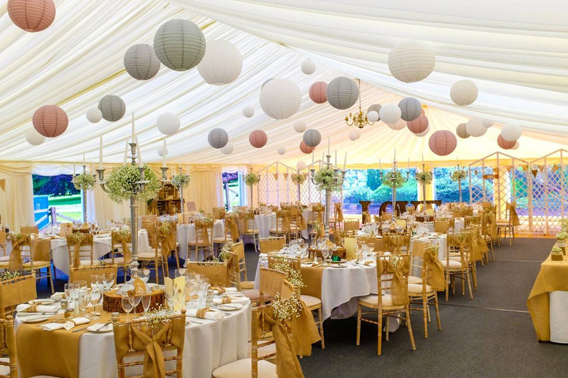Wedding dining area in a lantern decorated marquee