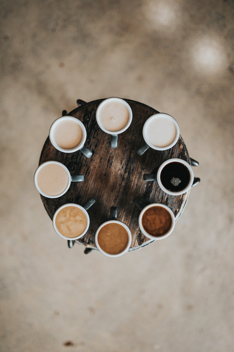 Dark wooden round table with cups of coffee of different strengths arranged in a circle around its edge