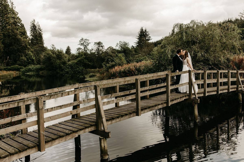 Bride and groom on a bridge over a river