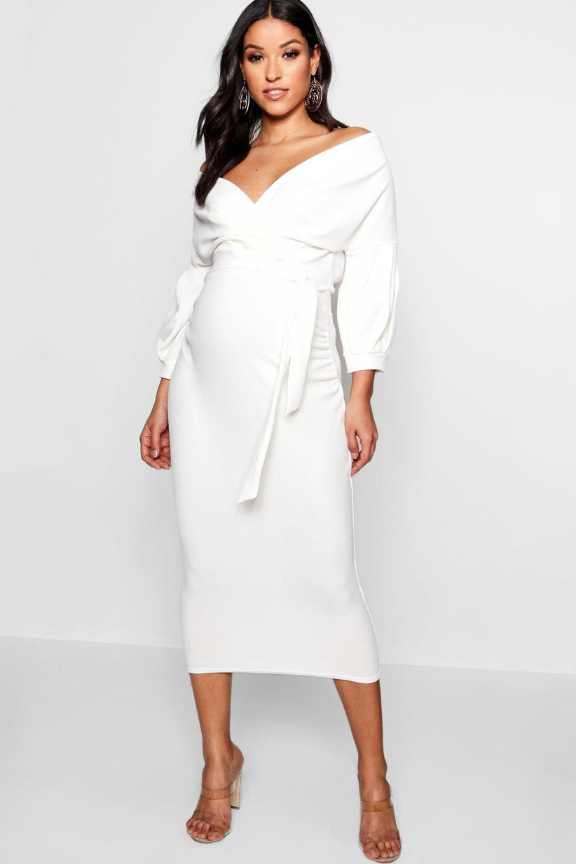 Model wearing a fitted off the shoulder white maternity dress