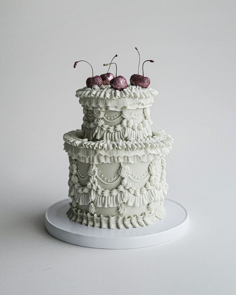 Pastel green tiered wedding cake with frills and cherries