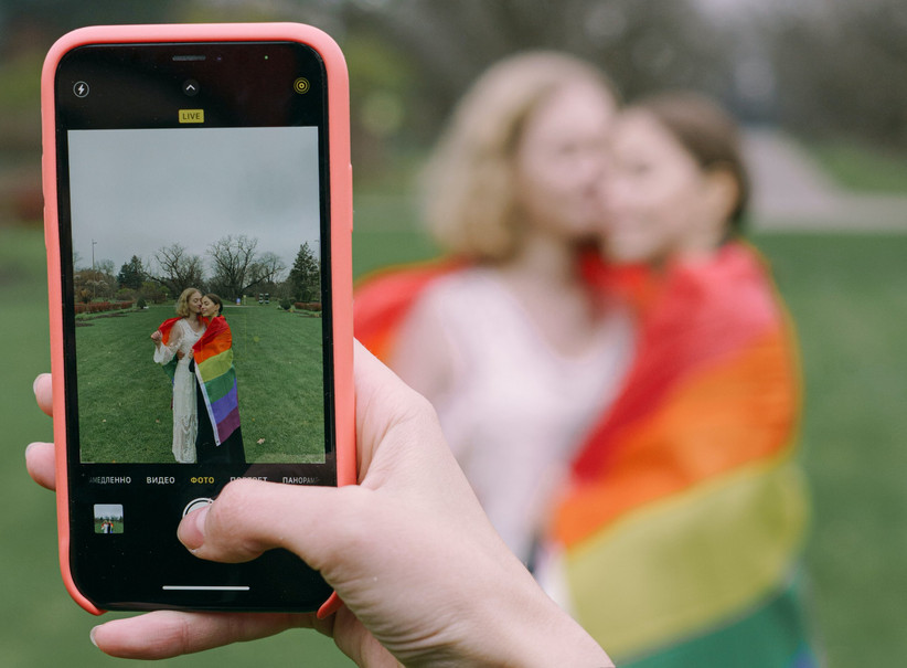 Same sex female couple posing for a photo wrapped in a rainbow flag