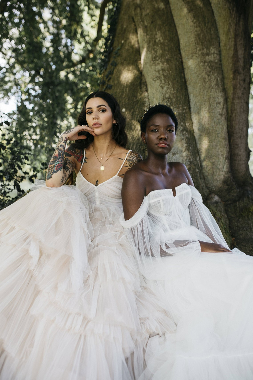 Two brides sit by a tree