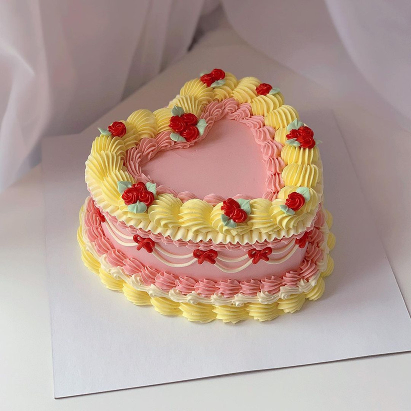 Heart shaped pink and yellow wedding cake with rose buds