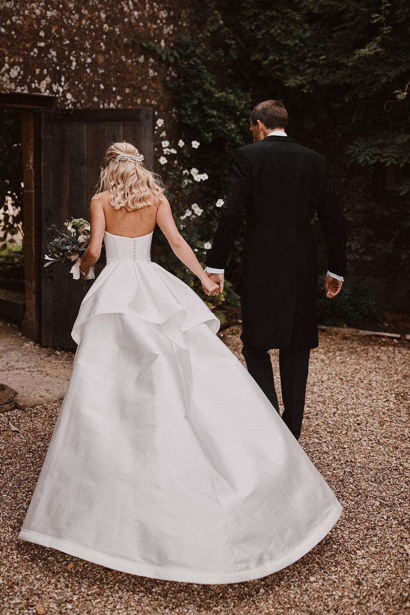 Bride and groom holding hands walking away