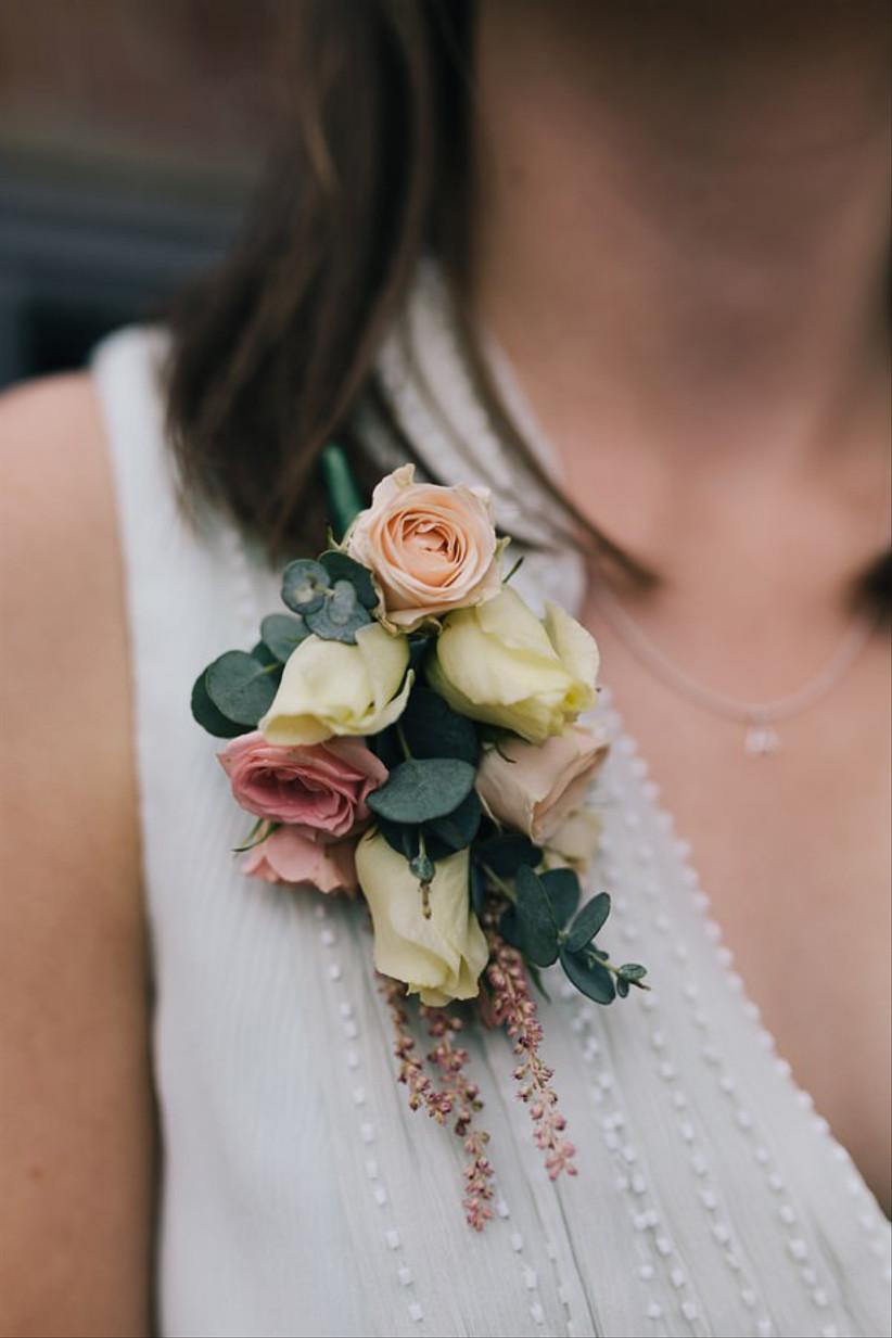 Bride wearing a rustic rose wedding buttonhole