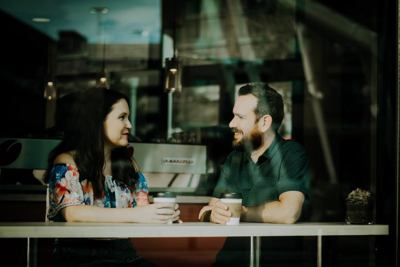 Heterosexual couple sitting in the window of a coffee shop