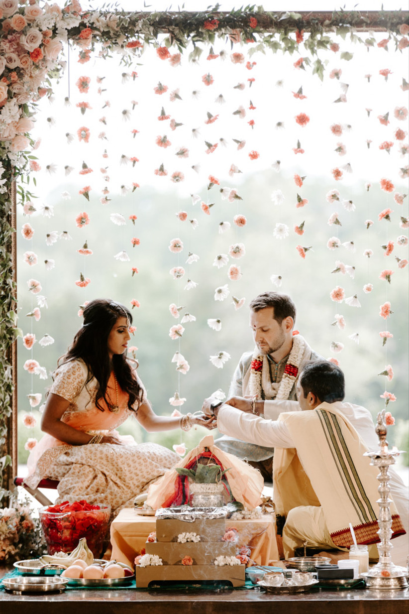 Bride and groom marry at a wedding ceremony by a suspended curtain of flowers