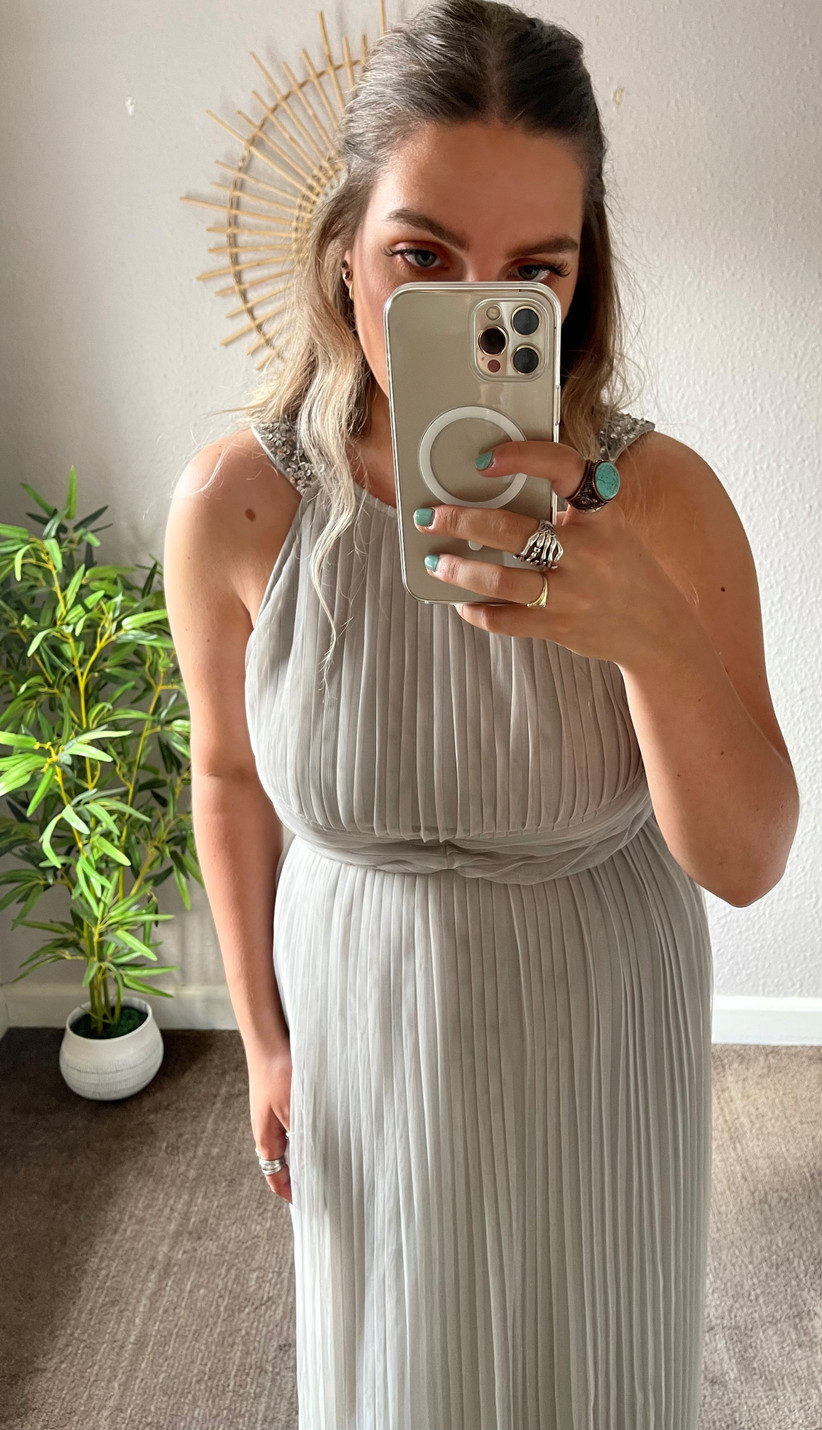 Model wearing a pleated maxi bridesmaid dress