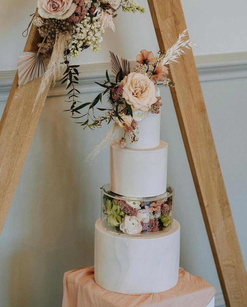 Clear wedding cake stand filled with flowers