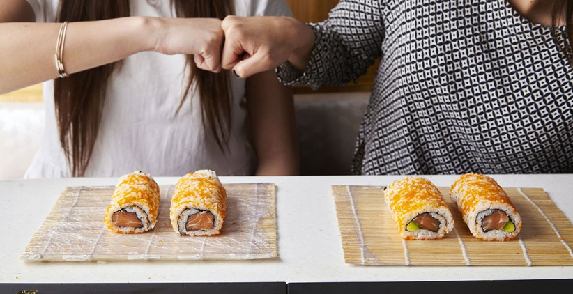 Couple making sushi rolls and fist bumping