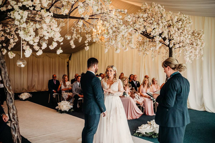 Bride and groom exchanging their vows in a marquee with white floral decorations