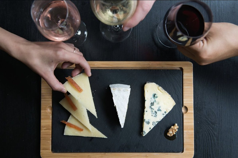 Three white people drinking different wines and eating from a slate cheeseboard