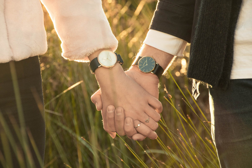 Couple wearing watches hold hands