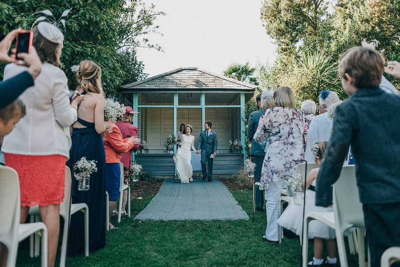 Outside wedding ceremony with a bride and groom walking back down the aisle