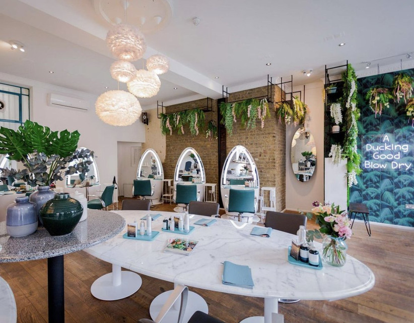 White and green hair salon with wooden floors, hanging foliage and flowers and exposed brick walls