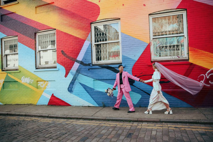 Couple hold hands next to a colourful wall